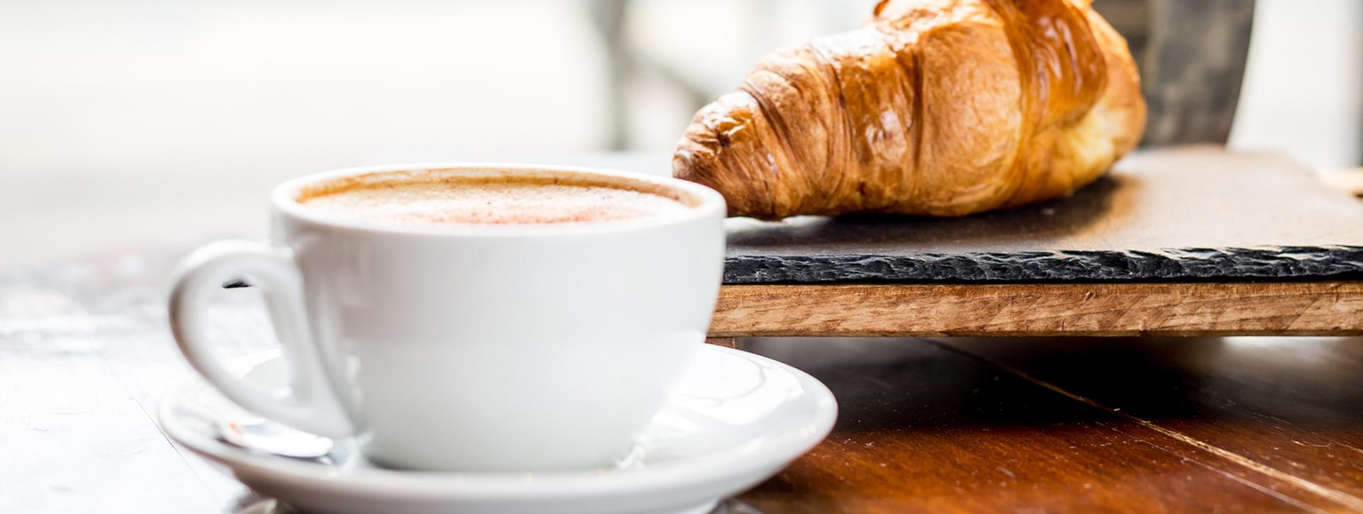 kahvi ja croisant kahvilapöydällä